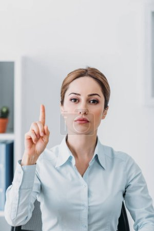 serious adult businesswoman looking at camera and pointing up at office