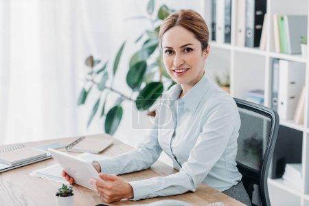 Photo pour Belle femme d'affaires travaillant avec pastilles au bureau et en regardant la caméra de sourire - image libre de droit