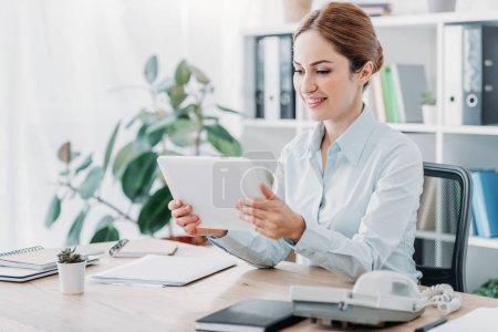 Photo pour Belle femme d'affaires travaillant avec pastilles au bureau de sourire - image libre de droit