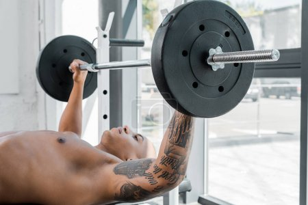 athletic bare-chested tattooed sportsman lying on bench and lifting barbell in gym
