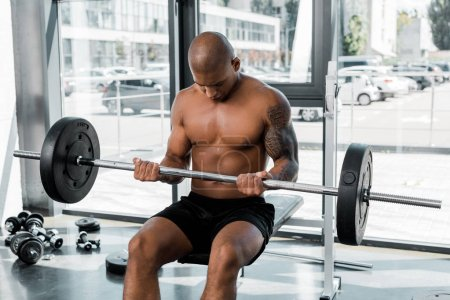 athletic bare-chested african american sportsman sitting on bench and lifting barbell in gym