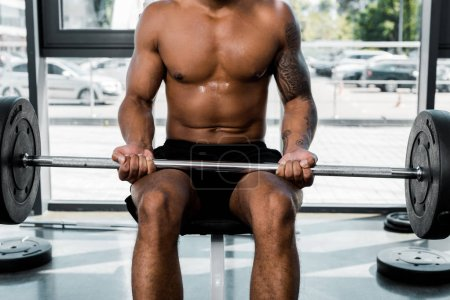 cropped shot of muscular tattooed sportsman sitting on bench and holding barbell in gym