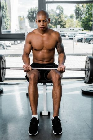athletic young african american sportsman sitting on bench and lifting barbell in gym