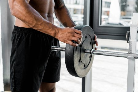 Photo for Cropped shot of muscular young sportsman putting weight plate on barbell in gym - Royalty Free Image