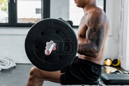 cropped shot of muscular sportsman sitting on bench and lifting barbell in gym