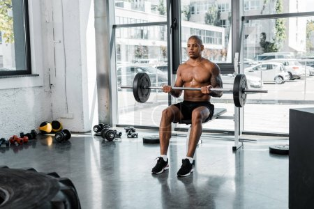 muscular african american sportsman sitting on bench and lifting barbell in gym