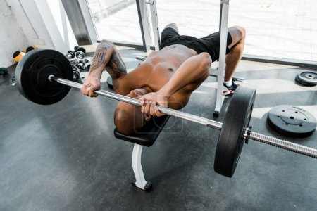 high angle view of muscular african american sportsman lying on bench and lifting barbell in gym