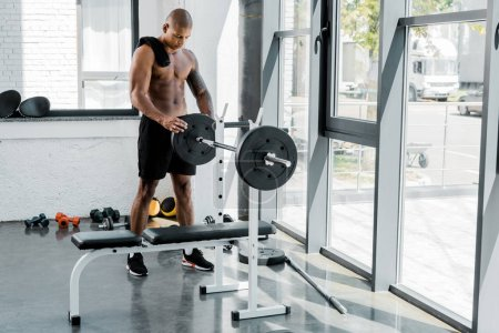 muscular young sportsman with towel training with barbell in gym