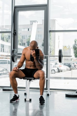 muscular young sportsman wiping forehead with towel while sitting after workout in gym