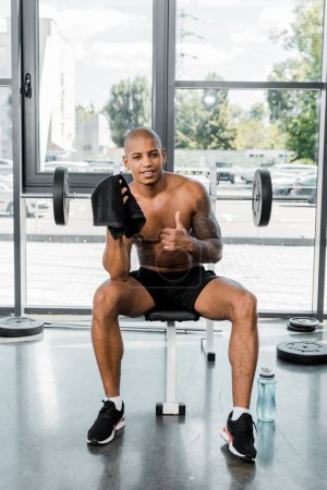 muscular young african american sportsman with towel showing thumb up and smiling at camera in gym