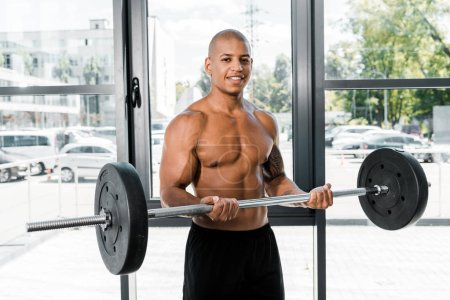 handsome muscular young sportsman holding barbell and smiling at camera in gym