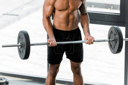 cropped shot of muscular bare-chested sportsman lifting barbell in gym