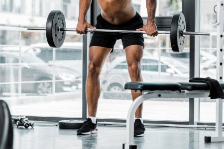 cropped shot of young athletic man lifting barbell in gym