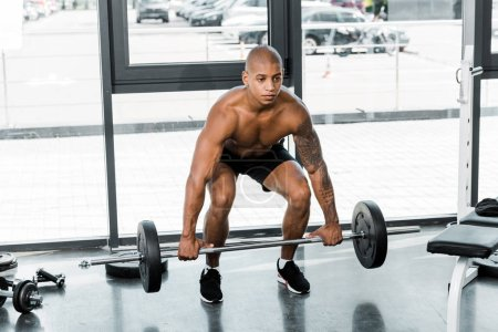 muscular shirtless young african american sportsman lifting barbell in gym