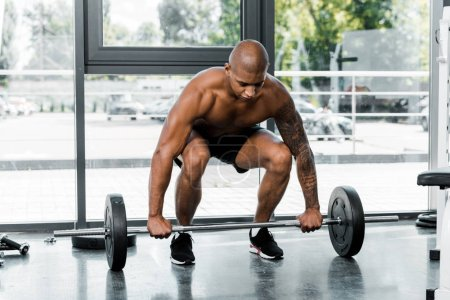 muscular bare-chested young african american man lifting barbell in gym