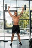 athletic bare-chested african american sportsman lifting barbell in gym