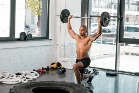 Photo for Muscular bare-chested young sportsman lifting barbell and looking away in gym - Royalty Free Image
