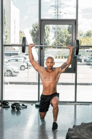 muscular bare-chested young sportsman lifting barbell in gym