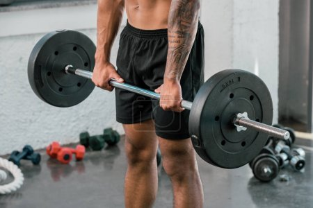 cropped shot of muscular young sportsman holding barbell in gym
