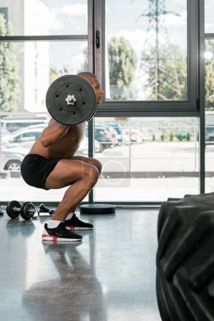 side view of young athletic african american man lifting barbell and looking away in gym
