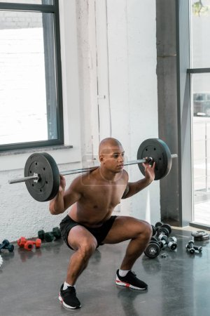 young athletic african american man lifting barbell and looking away in gym