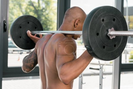 back view of muscular young sportsman lifting barbell in gym