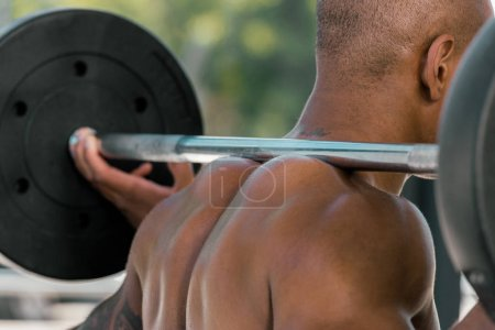 cropped shot of muscular african american sportsman lifting barbell in gym