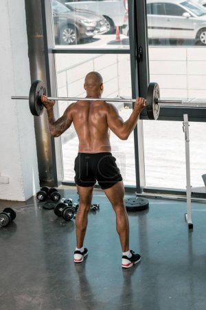 back view of athletic young shirtless man lifting barbell in gym
