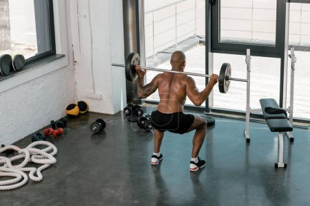 high angle view of muscular young man lifting barbell in gym