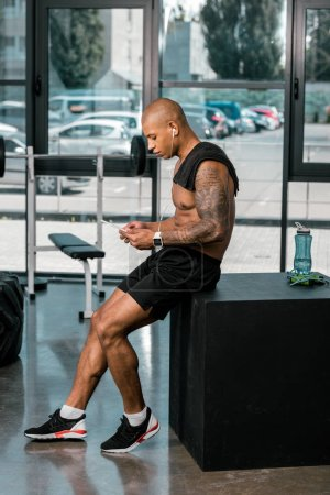 side view of muscular young tattooed african american sportsman using digital tablet in gym
