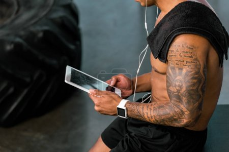 cropped shot of muscular tattooed sportsman using digital tablet in gym
