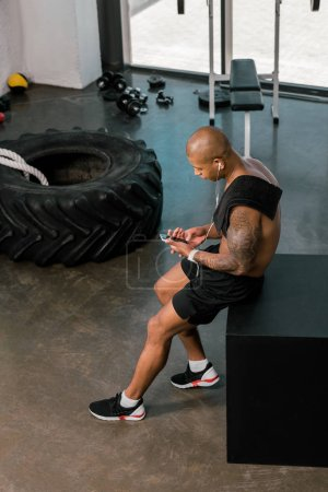 high angle view of muscular young sportsman in earphones sitting and using smartphone in gym