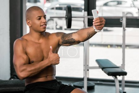 smiling muscular african american man showing thumb up and taking selfie with smartphone in gym