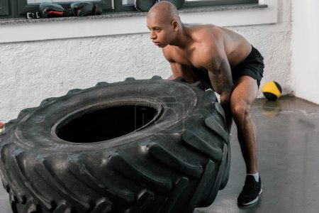 young muscular bare-chested african american sportsman training with tyre in gym