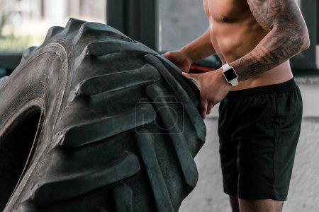 cropped shot of muscular shirtless man exercising with tyre in gym