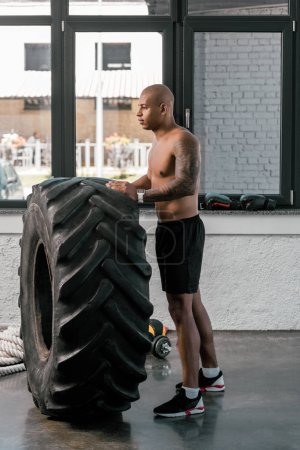 side view of muscular young man training with tyre and looking away in gym