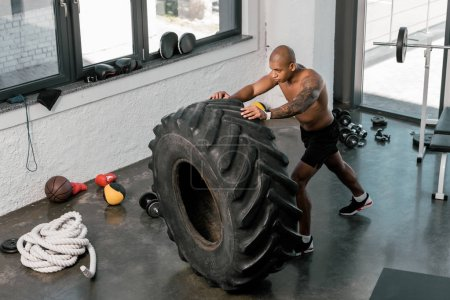 Photo for High angle view of muscular young african american man training with tyre in gym - Royalty Free Image