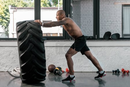side view of muscular shirtless man training with tyre in gym