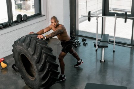 Photo for High angle view of muscular young man training with tyre and smiling at camera in gym - Royalty Free Image
