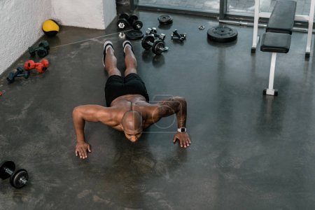 high angle view of muscular shirtless young man doing push ups in gym