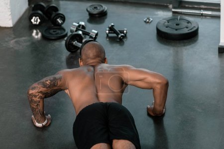 Photo for High angle view of shirtless young man doing push ups in gym - Royalty Free Image