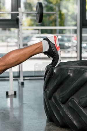 Photo for Cropped shot of muscular male leg on tire in gym - Royalty Free Image