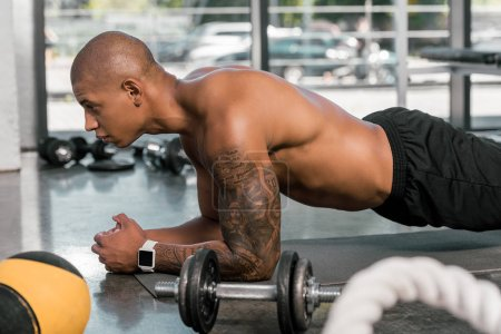 side view of tattooed african american sportsman doing plank at gym