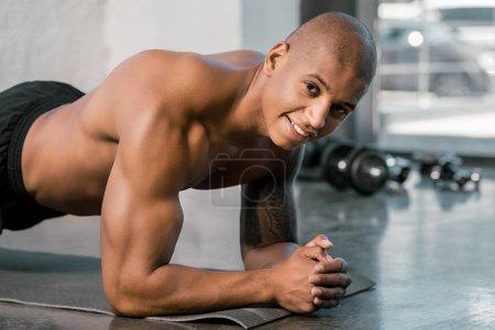 sportif afro-américain heureux, faisant la planche sur les tapis de remise en forme au gymnase