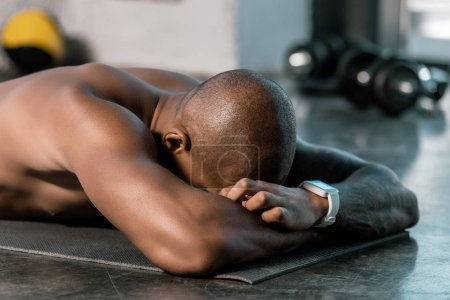 selective focus of african american athlete resting on fitness mat at gym