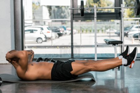 selective focus of african american man doing abs on fitness mat at gym