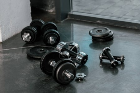 selective focus of iron dumbbells on floor at gym