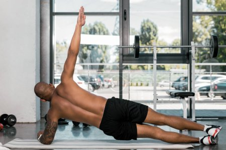 rear view of muscular african american man exercising on fitness mat at gym