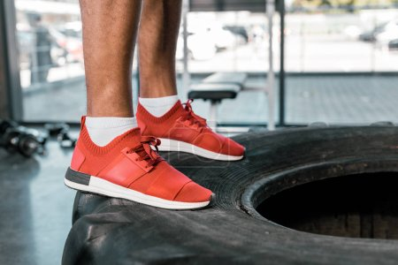 low section of sportsman in red sneakers standing on tire at gym