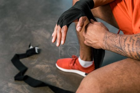 partial view of tattooed african american sportsman wrapping hand in boxing bandage at gym